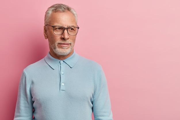Starszy mężczyzna ubrany w niebieską koszulę i okulary