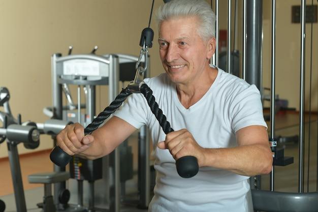 Starszy mężczyzna uprawiający sport na siłowni
