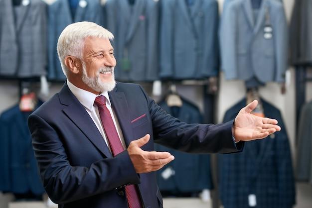 Starszy mężczyzna uśmiecha wybór kostiumów w sklepie.