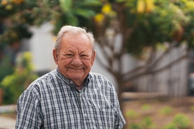 Starszy mężczyzna uśmiechający się po dniu pracy na farmie