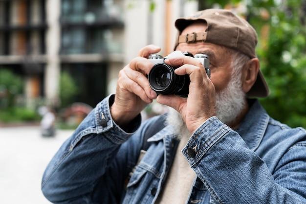Starszy mężczyzna używa aparatu na zewnątrz w mieście do robienia zdjęć