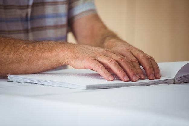Starszy mężczyzna używa braille'a do czytania