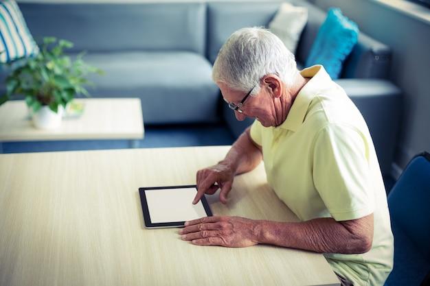 Starszy mężczyzna używa cyfrową pastylkę