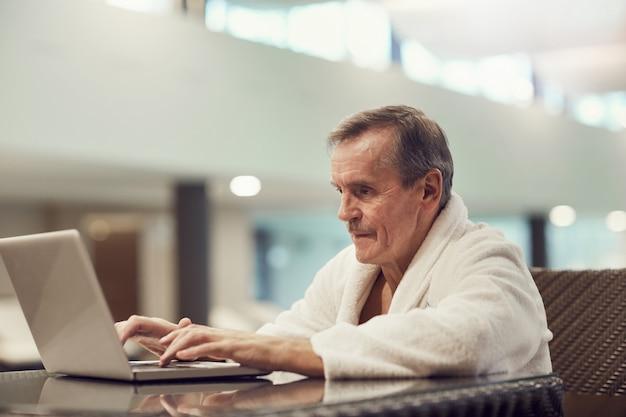 Starszy mężczyzna używa laptop w centrum spa