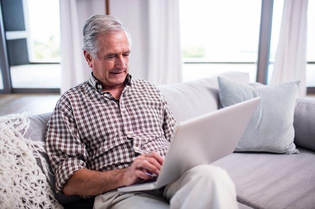Starszy mężczyzna używa laptop w żywym pokoju