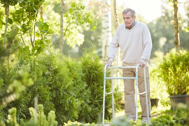 Starszy mężczyzna używa piechura w parku