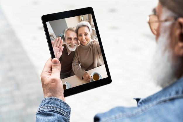 Starszy mężczyzna używa tabletu na zewnątrz w mieście do wideorozmów