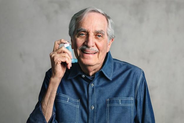 Starszy mężczyzna używający inhalatora