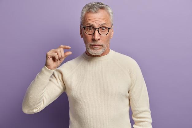 Starszy mężczyzna w białym swetrze i okularach