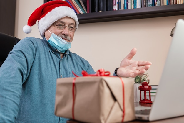 Starszy mężczyzna w czapce świętego mikołaja rozmawia za pomocą laptopa dla przyjaciół i dzieci połączeń wideo. pokój jest odświętnie urządzony. boże narodzenie w okresie koronawirusa.