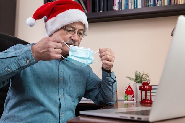 Starszy mężczyzna w czapce świętego mikołaja zakłada maskę i rozmawia za pomocą urządzenia przenośnego. pokój jest odświętnie urządzony. boże narodzenie w okresie koronawirusa.
