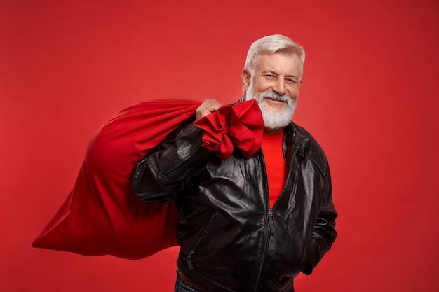 Starszy mężczyzna w czerwonym swetrze i czarnej kurtce z dużym workiem świętego mikołaja