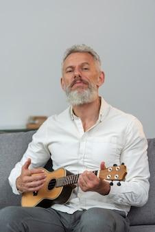 Starszy mężczyzna w domu gra na ukulele na kanapie