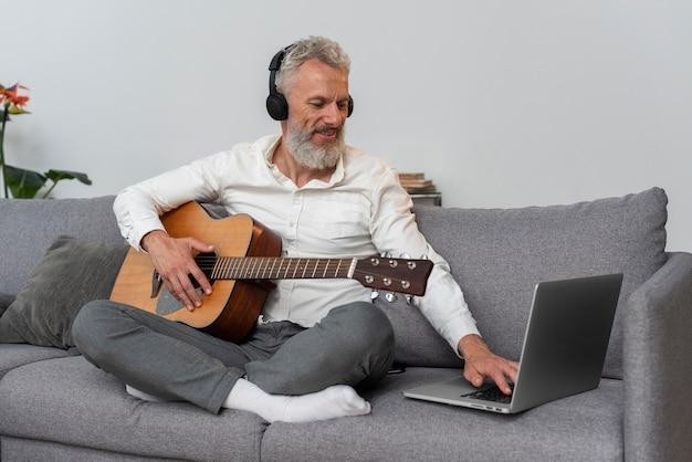 Starszy mężczyzna w domu na kanapie za pomocą laptopa do nauki lekcji gry na gitarze