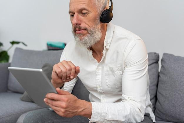 Starszy Mężczyzna W Domu Na Kanapie Za Pomocą Tabletu I Słuchawek Darmowe Zdjęcia
