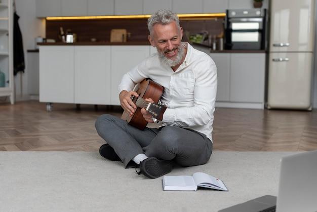 Starszy mężczyzna w domu na podłodze, biorąc lekcje gry na gitarze