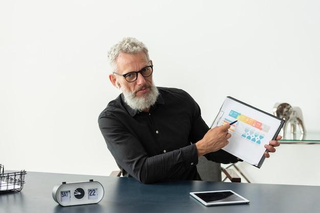Starszy mężczyzna w domu pokazuje wykres na notatniku z tabletem na biurku