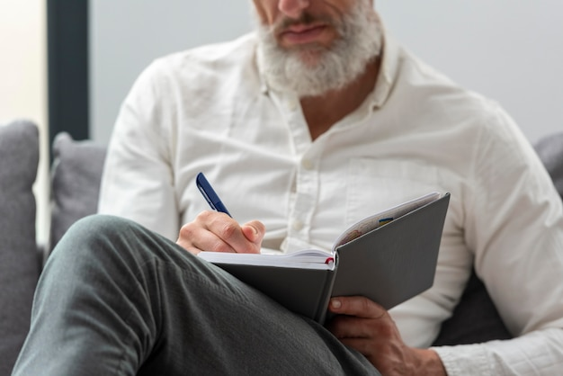 Starszy mężczyzna w domu studiuje i robi notatki