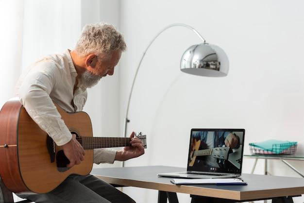 Starszy mężczyzna w domu studiuje lekcje gry na gitarze na laptopie