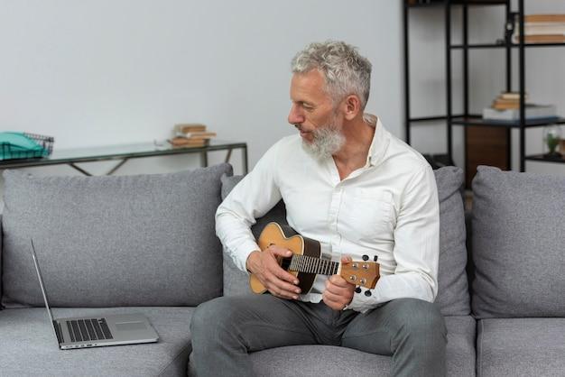 Starszy mężczyzna w domu studiuje lekcje gry na ukulele na laptopie