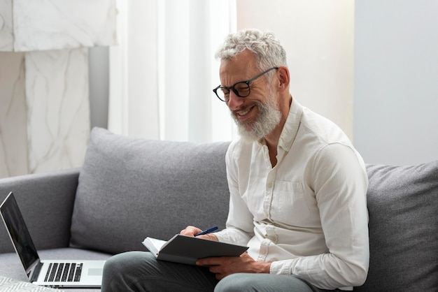Starszy Mężczyzna W Domu Studiuje Na Laptopie I Robi Notatki Darmowe Zdjęcia