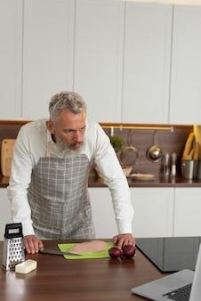 Starszy mężczyzna w domu w kuchni biorąc lekcje gotowania na laptopie
