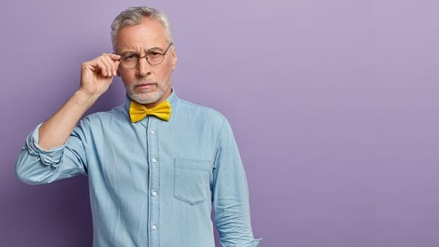 Starszy mężczyzna w dżinsowej koszuli i żółtej muszce