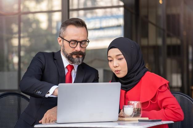 Starszy mężczyzna w eleganckim garniturze mówi do islamskiej kobiety przy stoliku na świeżym powietrzu. prezentacja biznesowa koncepcja z technologią urządzenia przenośnego.
