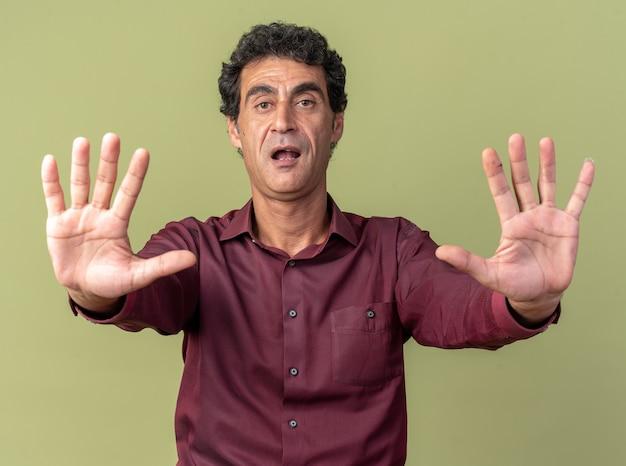 Starszy mężczyzna w fioletowej koszuli patrzący na kamerę przestraszony, wykonując gest zatrzymania z rękami trzymającymi się za ręce, stojąc nad zielenią