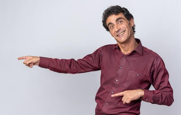 Starszy mężczyzna w fioletowej koszuli patrzący na kamerę szczęśliwy i zaskoczony, wskazując palcami wskazującymi w bok, stojąc nad białymi