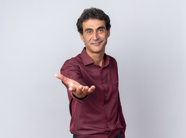 Starszy mężczyzna w fioletowej koszuli patrzący na kamerę uśmiechający się przyjazny, robiąc tu gest z ręką stojącą nad białymi