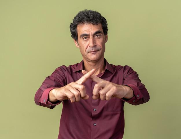 Starszy mężczyzna w fioletowej koszuli patrzący na kamerę z poważną twarzą krzyżującą palce, wykonujący gest obrony stojący nad zielenią