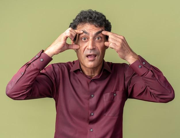 Starszy mężczyzna w fioletowej koszuli patrzący na kamerę zdumiony i zaskoczony szeroko otwierającymi się oczami z palcami stojącymi nad zielenią