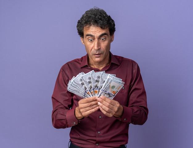 Starszy mężczyzna w fioletowej koszuli trzymający gotówkę patrzący na pieniądze zdumiony i zaskoczony stojąc na niebieskim tle