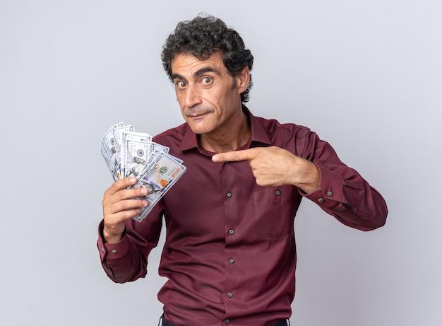 Starszy mężczyzna w fioletowej koszuli trzymający gotówkę wskazującą palcem wskazującym na pieniądze, wyglądający na zaskoczony i szczęśliwy