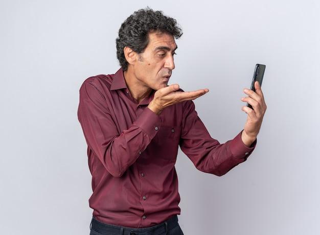 Starszy mężczyzna w fioletowej koszuli trzymający smartfona, patrzący na ekran, dmuchający pocałunkiem, stojący na białym