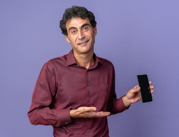Starszy mężczyzna w fioletowej koszuli trzymający smartfona, prezentujący go ręką, uśmiechający się pewnie stojąc na niebieskim tle