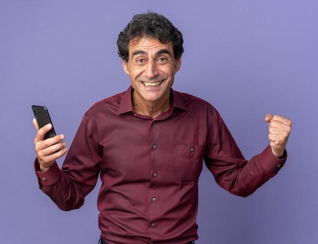 Starszy mężczyzna w fioletowej koszuli trzymający smartfona zaciskający pięść szczęśliwy i podekscytowany