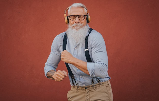 Starszy mężczyzna w hipsterskich ubraniach i okularach z długą białą brodą słucha muzyki i radośnie tańczy na ulicy