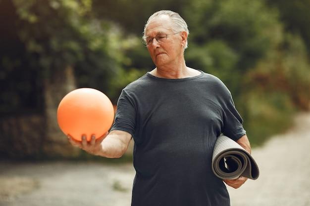 Starszy mężczyzna w lato park. grangfather używa piłki.