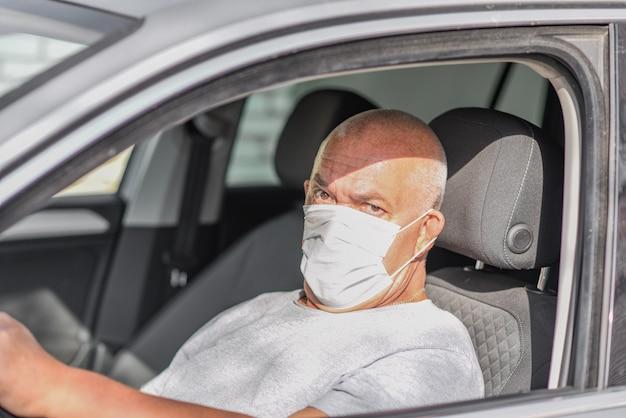 Starszy mężczyzna w masce medycznej podczas prowadzenia samochodu, patrząc w kamerę. koncepcja koronawirusa