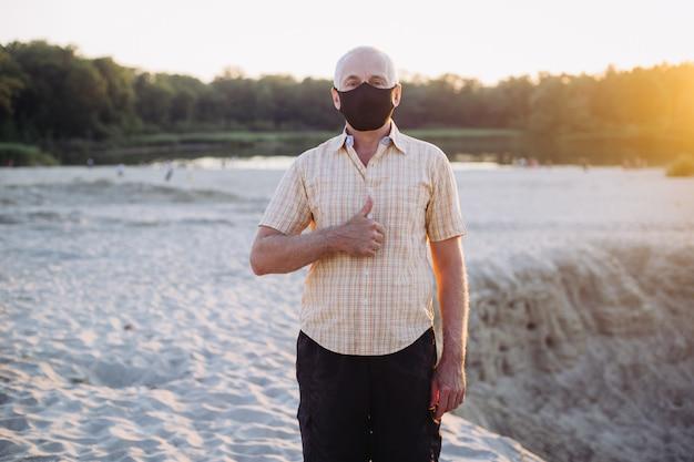 Starszy mężczyzna w masce ochronnej pokazujący kciuk do góry, koronawirus, choroba, infekcja, kwarantanna, maska medyczna