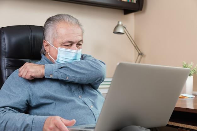 Starszy mężczyzna w masce pracuje lub komunikuje się na laptopie w domu. nauka, szkolenia, praca, komunikacja, rozrywka, wypoczynek w okresie koronawirusa.