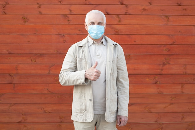 Starszy mężczyzna w medycznej masce w parku. ochrona przed chorobą. koncepcja bezpieczeństwa zdrowia
