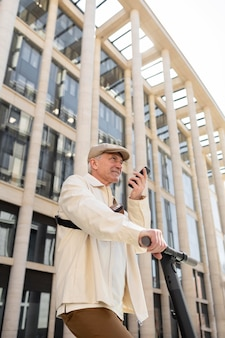 Starszy mężczyzna w mieście ze skuterem elektrycznym za pomocą smartfona using