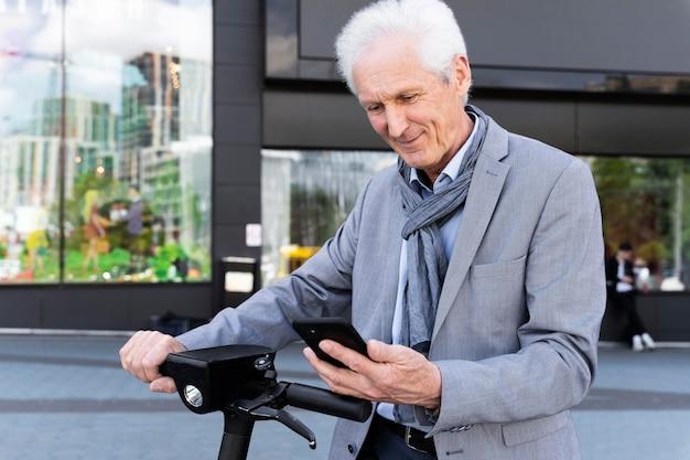 Starszy mężczyzna w mieście ze skuterem elektrycznym za pomocą smartfona