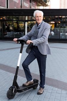 Starszy mężczyzna w mieście ze skuterem elektrycznym