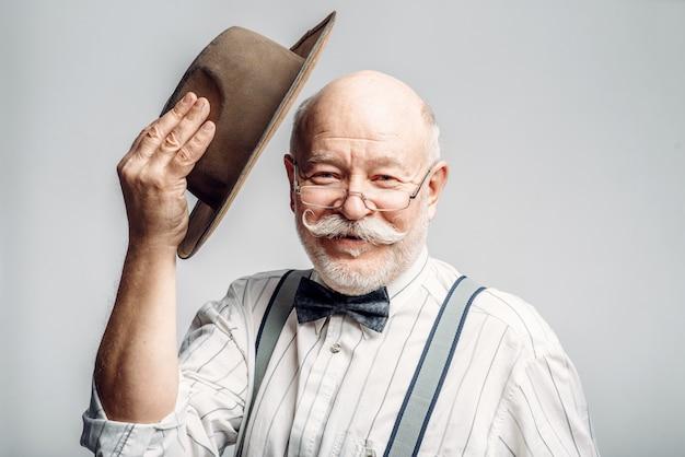 Starszy mężczyzna w muszce i okularach zdejmuje kapelusz, szare tło. dojrzały starszy patrząc na kamery w studio