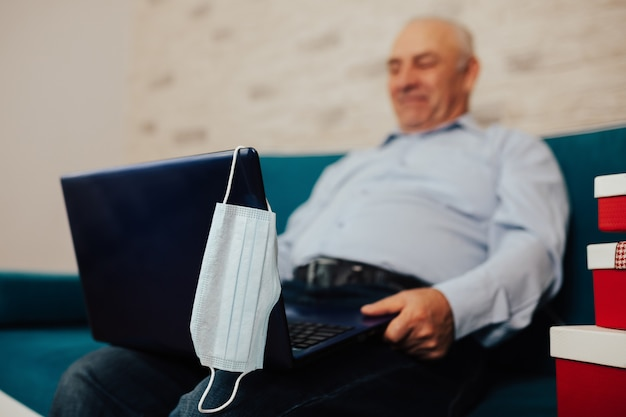 Starszy mężczyzna w niebieskiej koszuli nawiązywanie połączenia wideo na laptopie w salonie w domu podczas kwarantanny