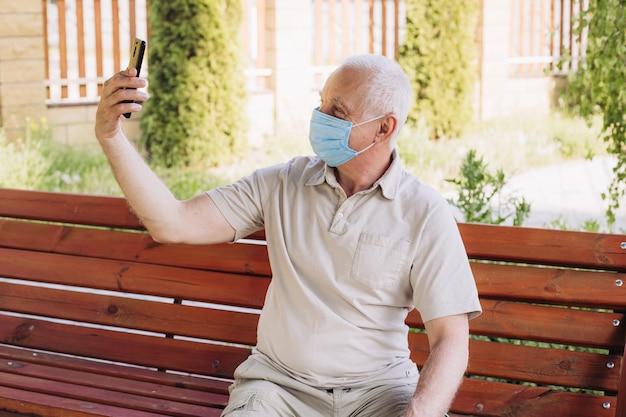 Starszy mężczyzna w ochronnej masce na twarz za pomocą smartfona, wybuch choroby wirusowej koronawirusa covid-2019